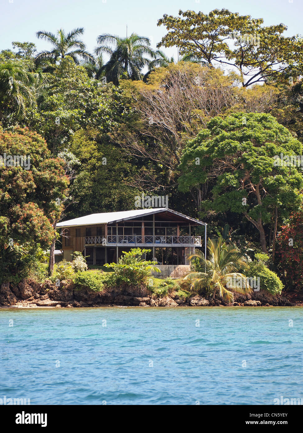 Waterfront Caribbean home surrounded by lush tropical vegetation, Bocas del Toro, Panama - Stock Image