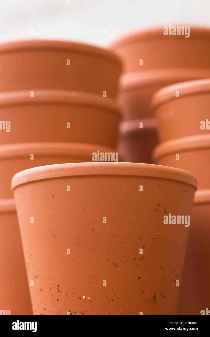 A stack of pots in the garden against a white wall. - Stock Image