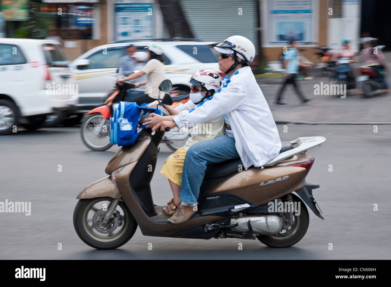 Schoolboy travelling home by motorbike, Saigon, Vietnam - Stock Image