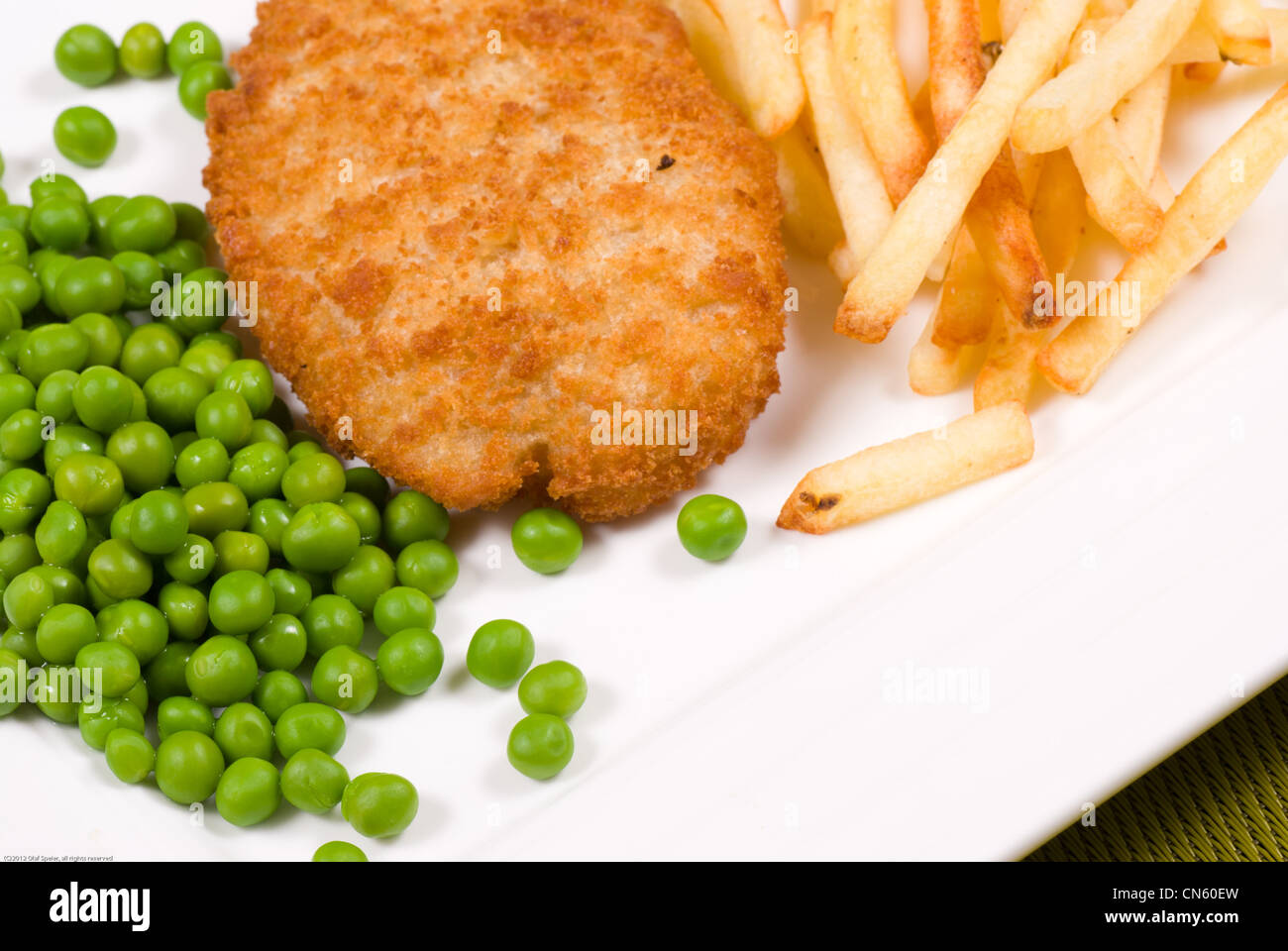 Breaded cod served with peas and fries - Stock Image