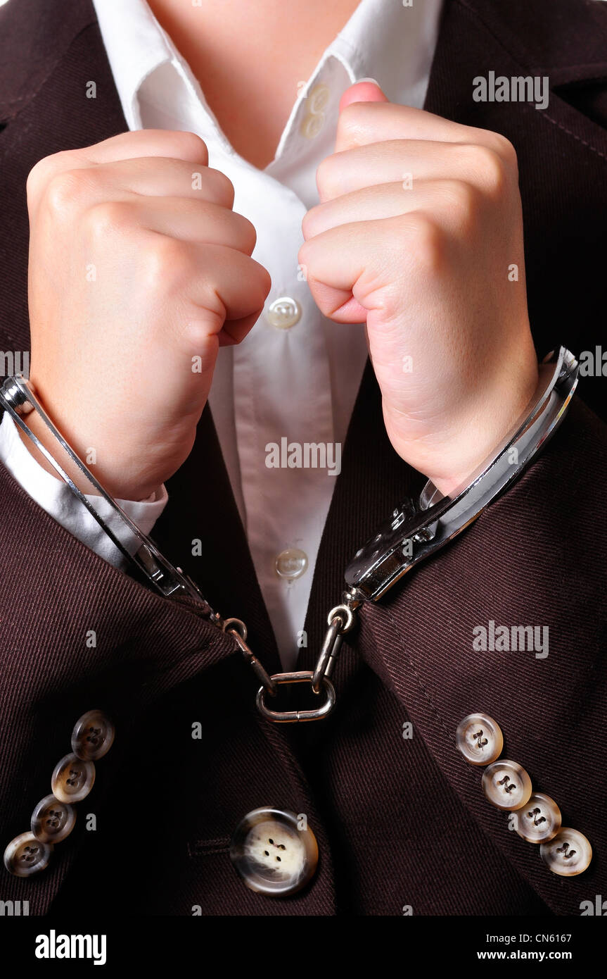 Closeup of an handcuffed businessperson in a brown suit - Stock Image