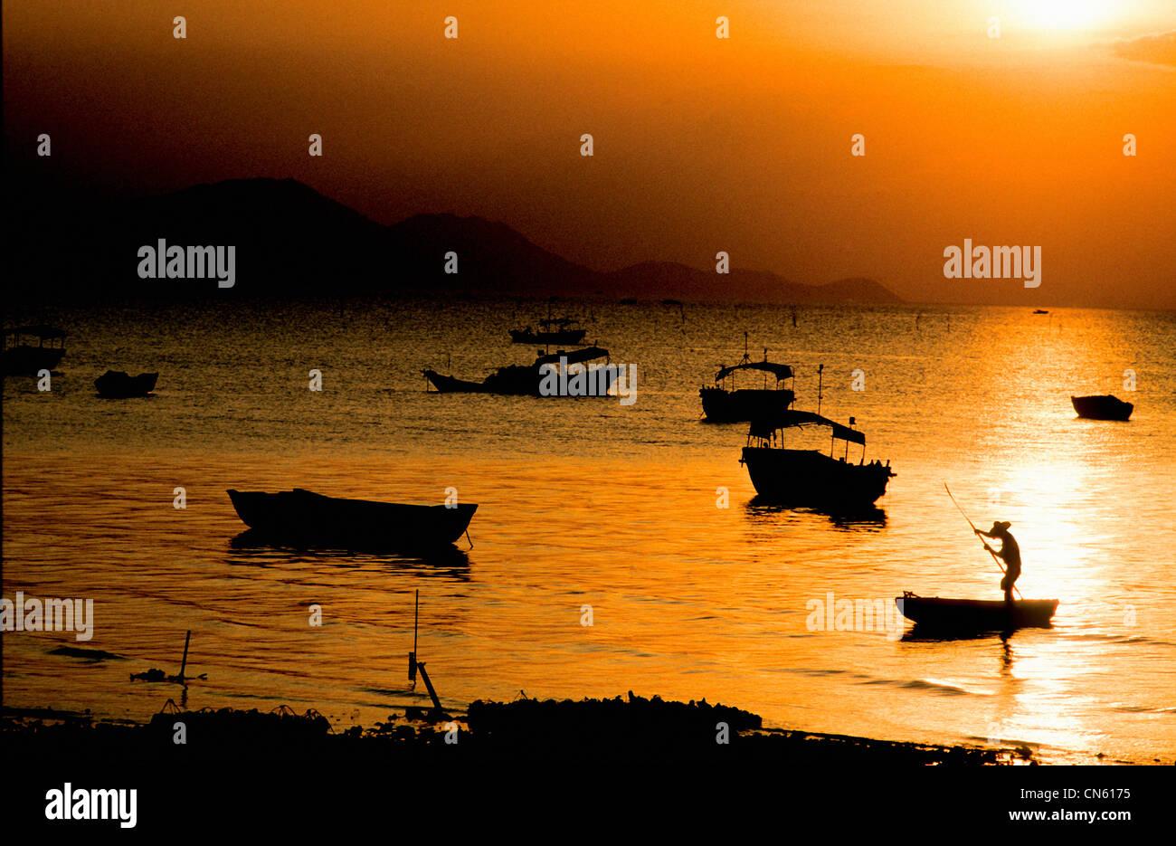fisherman poles sampan to beach at sunset at harbor in South China Sea New Territories Hong Kong China - Stock Image