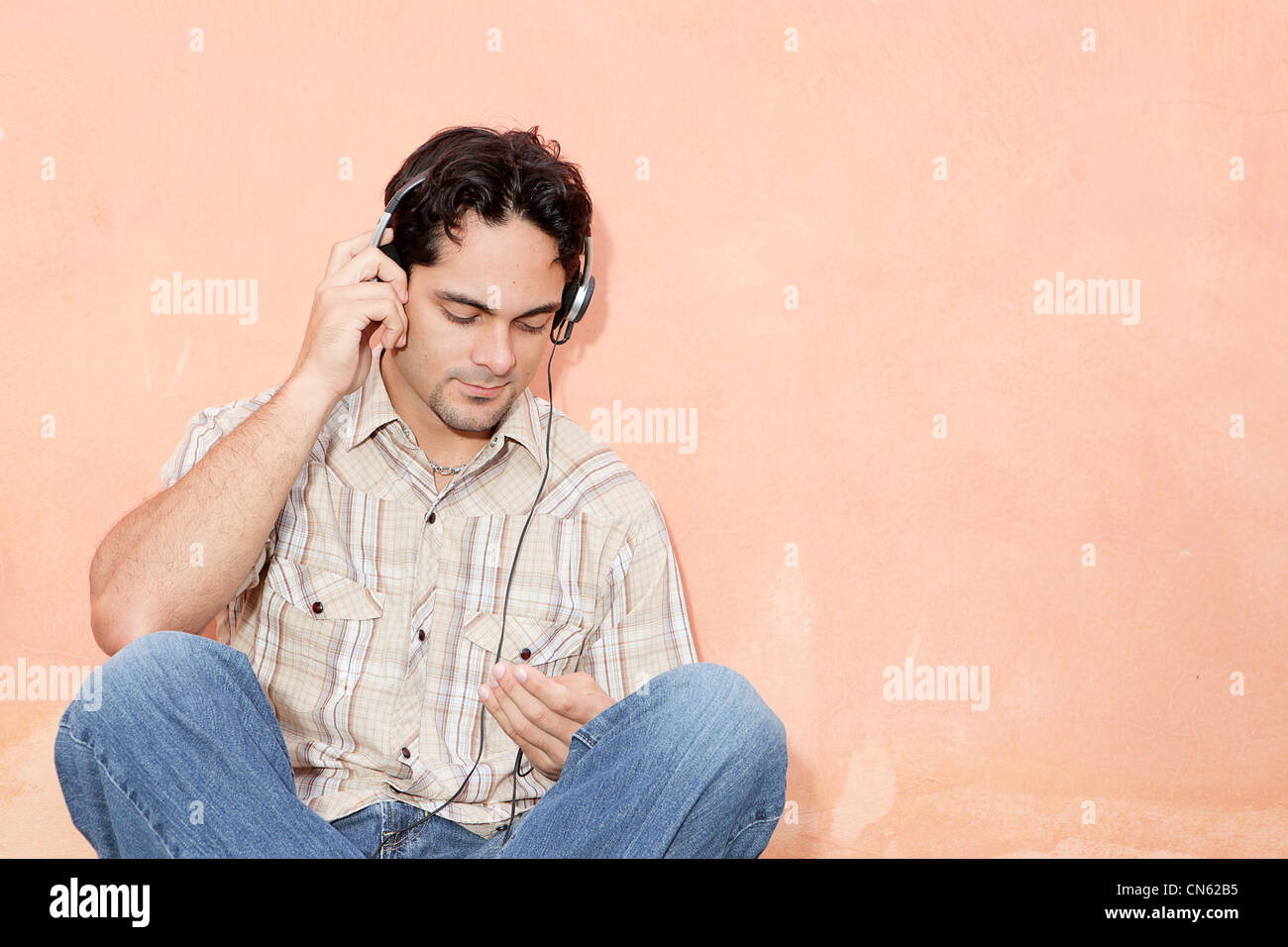 man listening to music with earphones and personal stereo - Stock Image