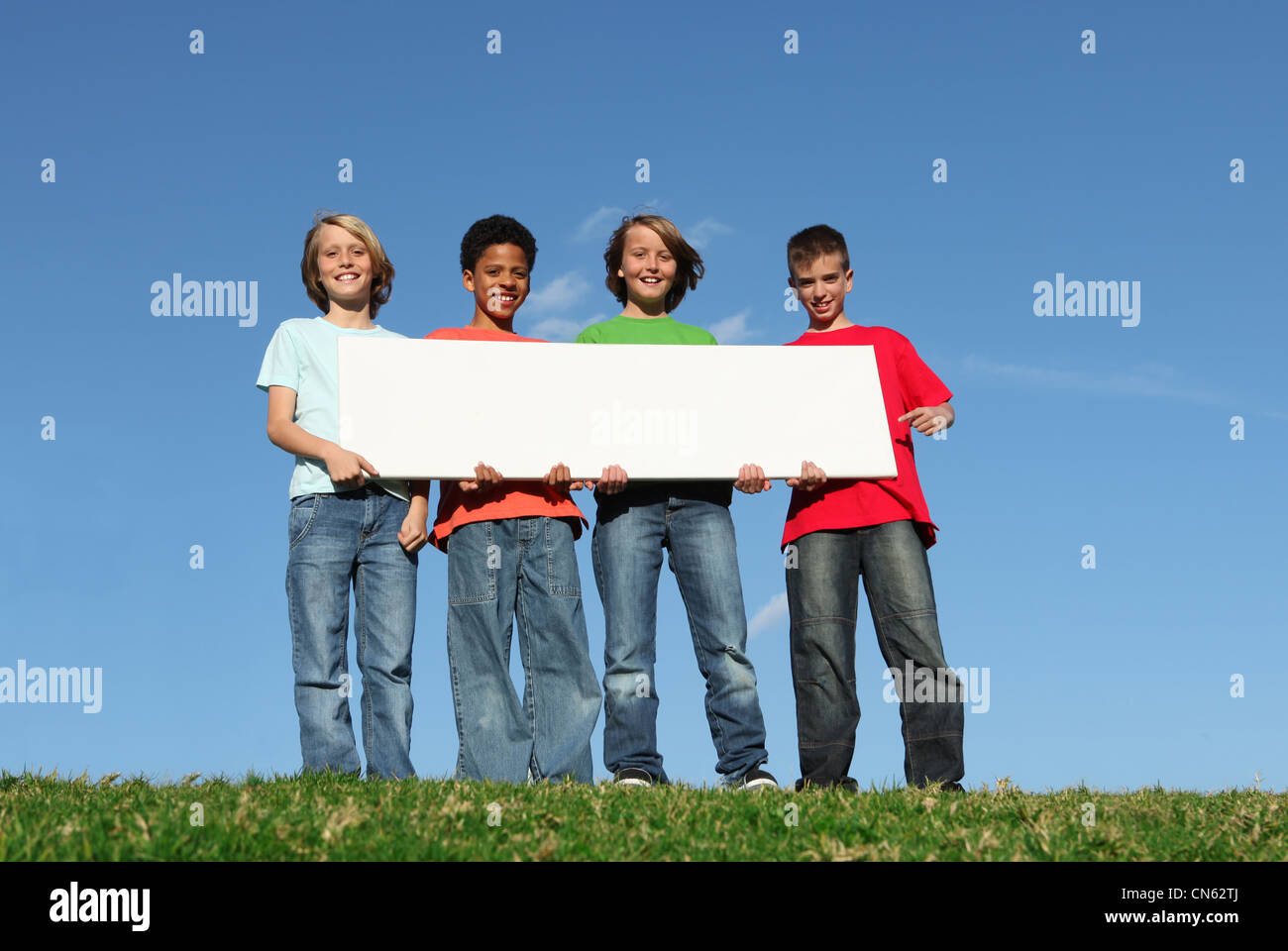 mixed race kids holding blank sign - Stock Image