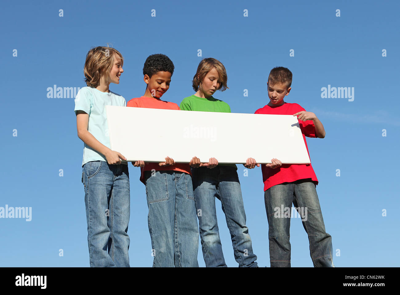 group of diverse kids holding white sign - Stock Image