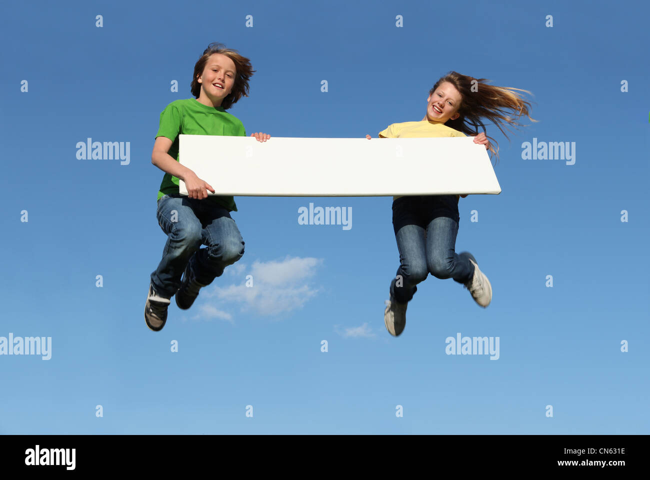 kids jumping holding blank sign - Stock Image