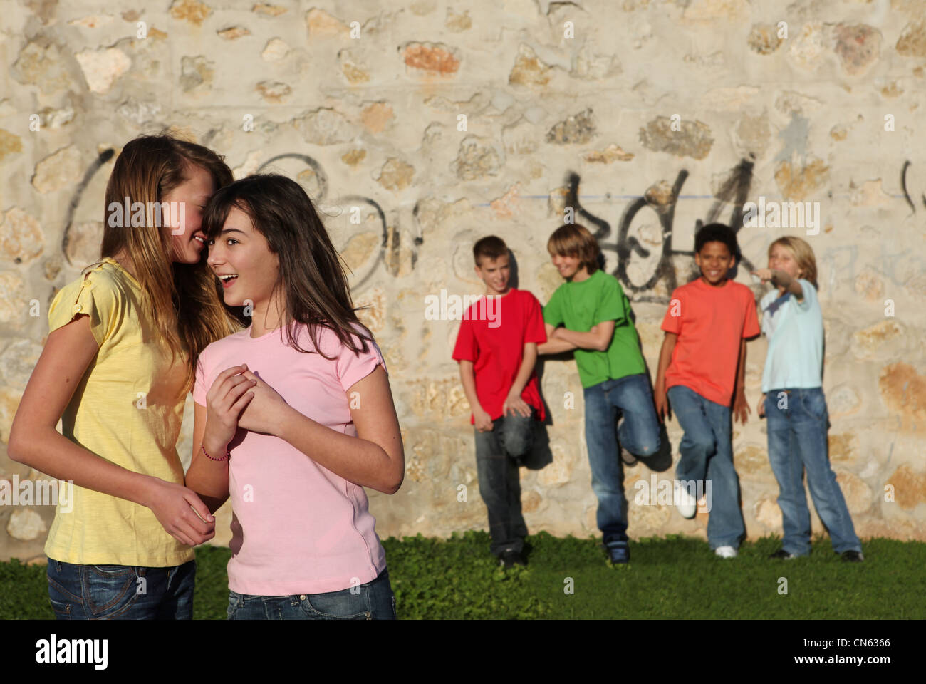 group of diverse teens hanging around out doors whispering secrets and flirting - Stock Image