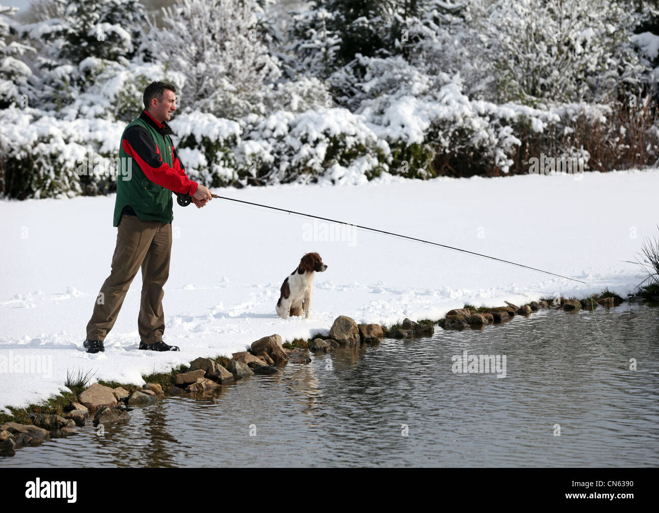 Man and his dog fishing at Lochter fishery near Oldmeldrum in Aberdeenshire, Scotland, UK - Stock Image