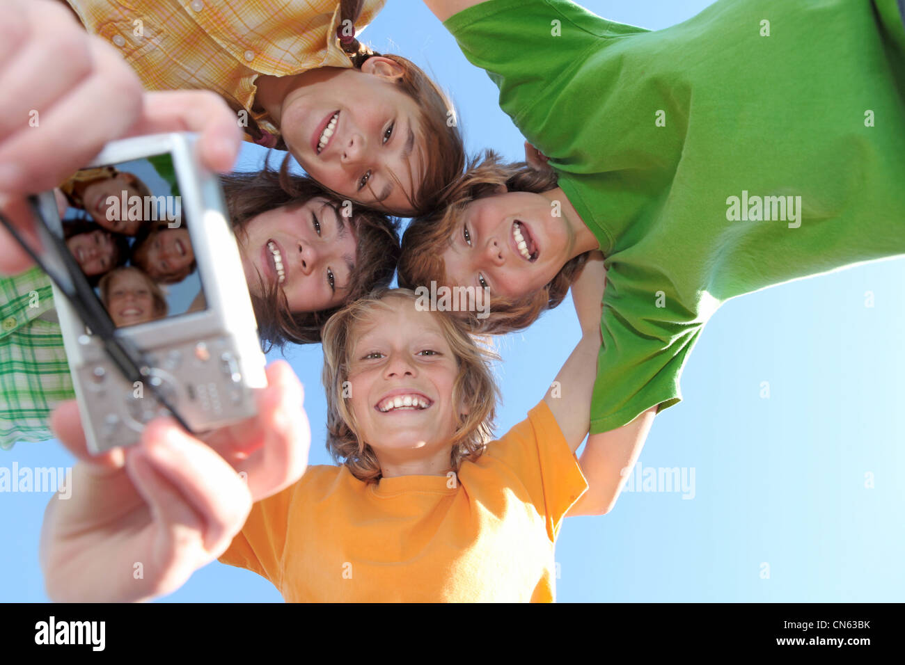 white teeth and smiles, happy group of kids taking photo with camera - Stock Image