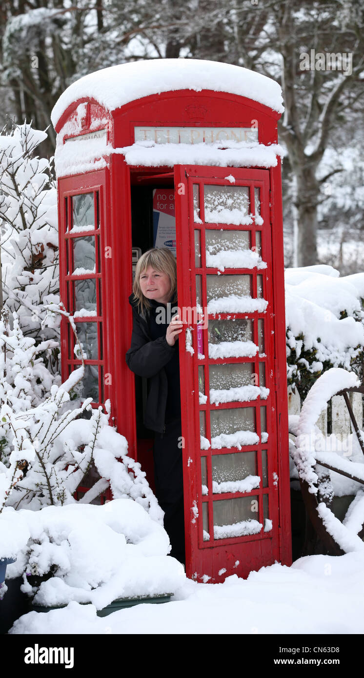Woman in snow covered rural public telephone box in winter in Scotland, UK - Stock Image