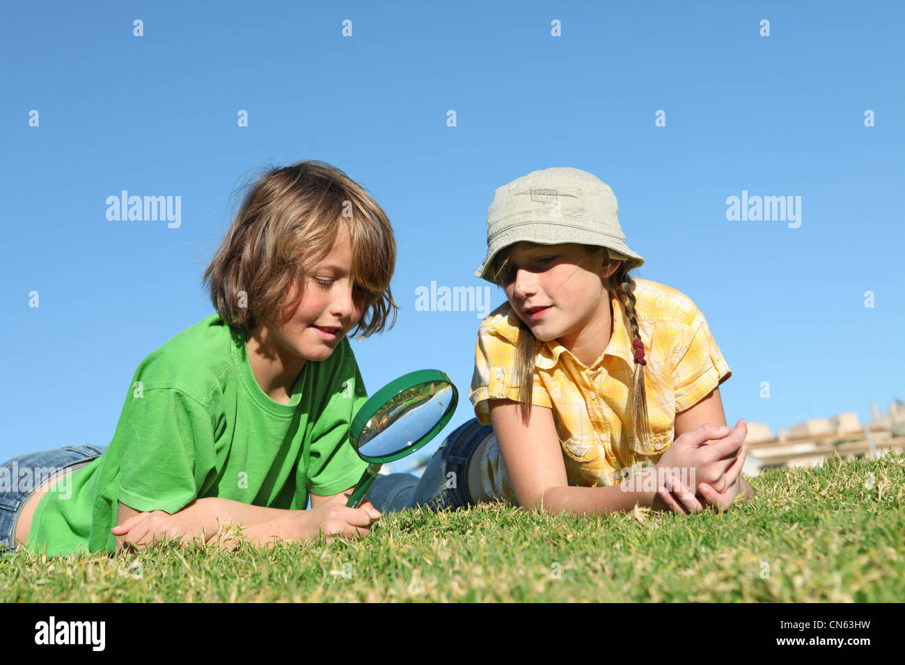 kids playing outdoors with magnifying, glass - Stock Image
