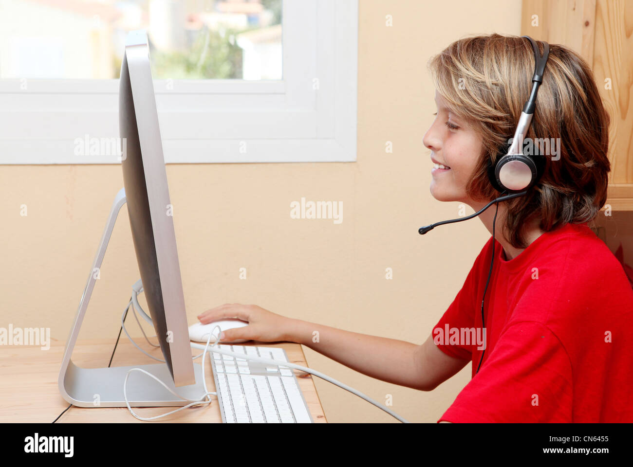 child with headphones or earphones listening to music or chatting on home or school pc computer - Stock Image