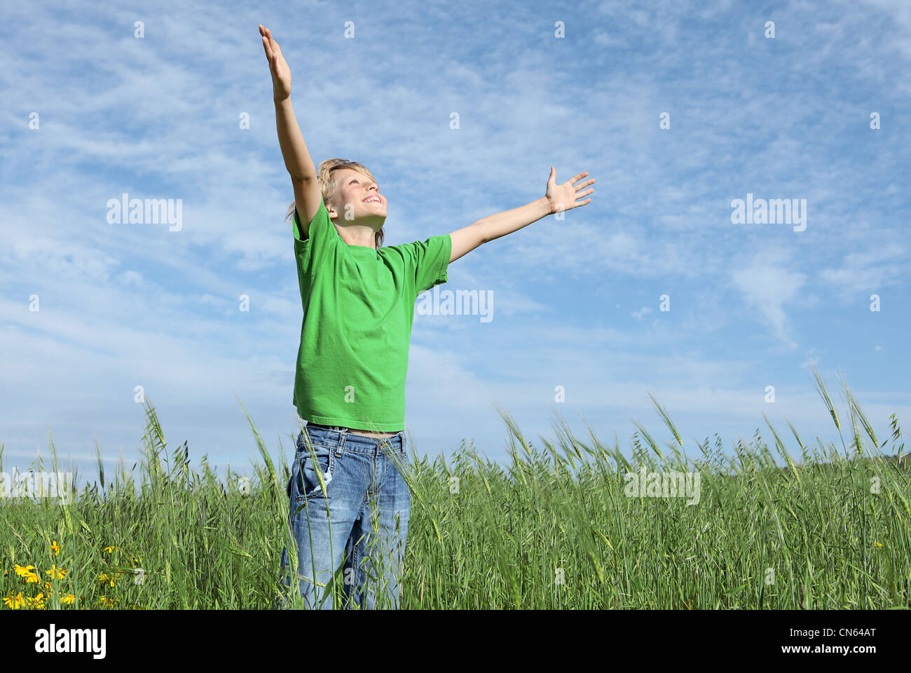 happy child arms raised praising the skies in summer - Stock Image