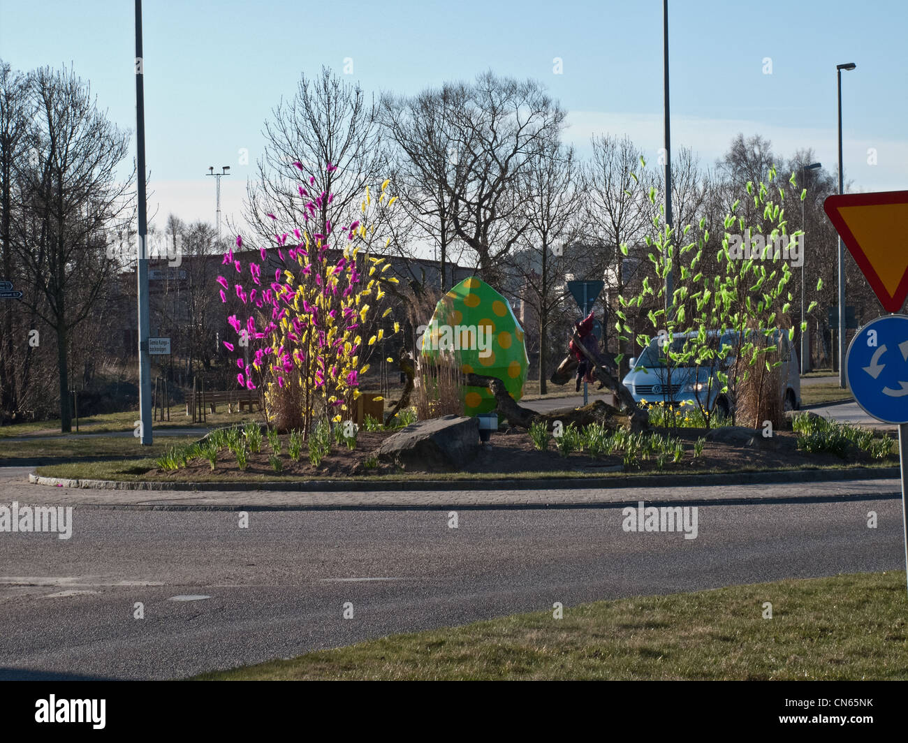 Roundabout with Easter feathers decorated trees. - Stock Image