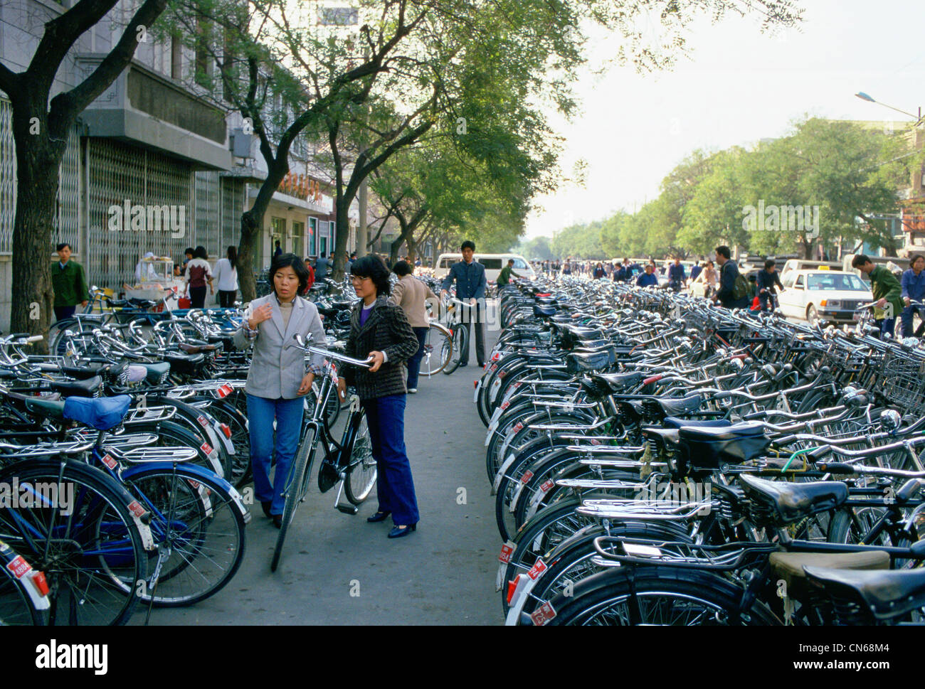 Young women parking bicycle in crowded bicycle park, Beijing, China - Stock Image