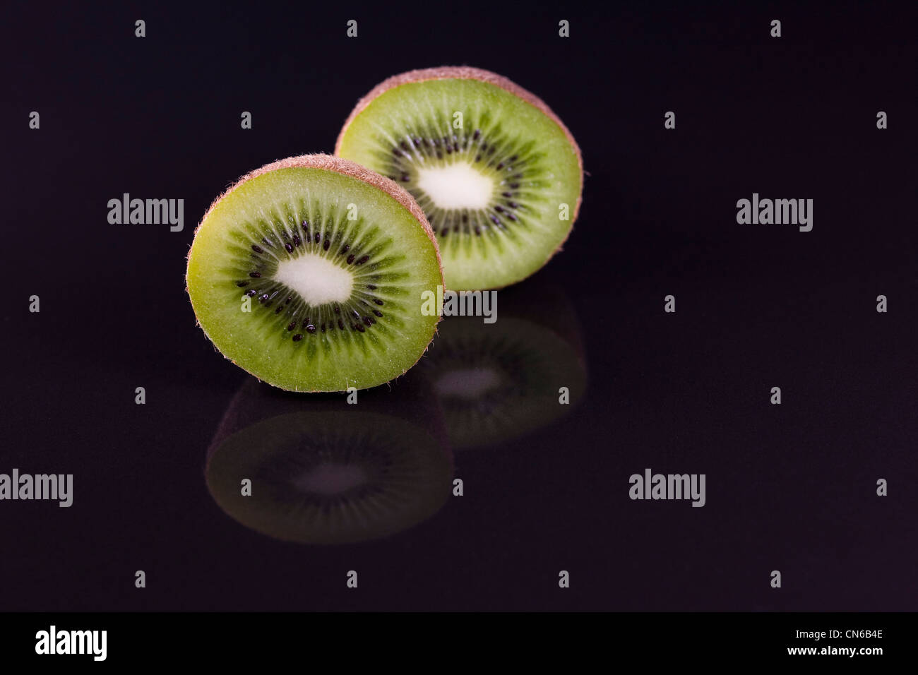 Actinidia deliciosa. Kiwi fruit cross section reflected on a black surface. Chinese gooseberry. - Stock Image
