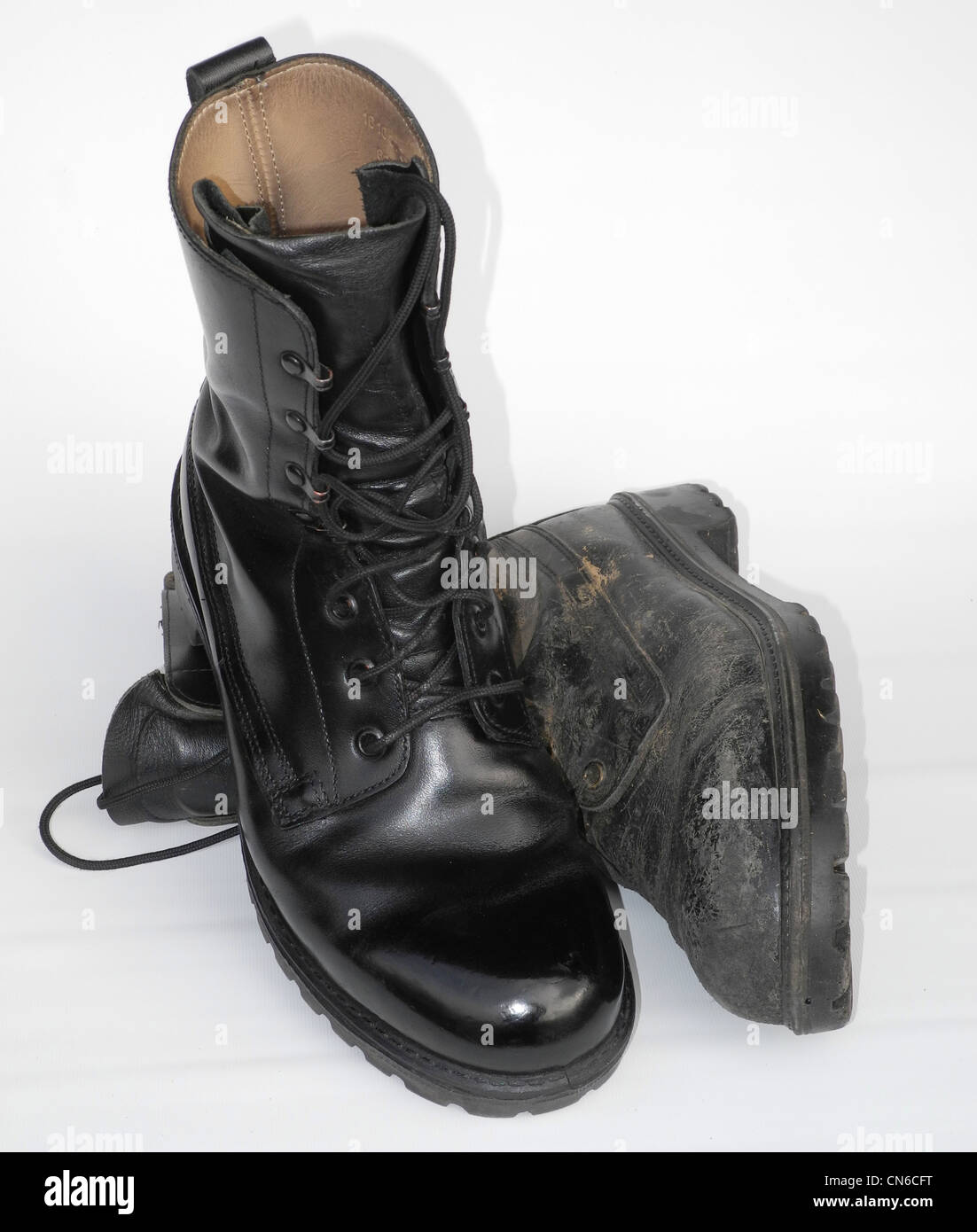 A well cared for military boot - army polished - with a well worn one - Stock Image