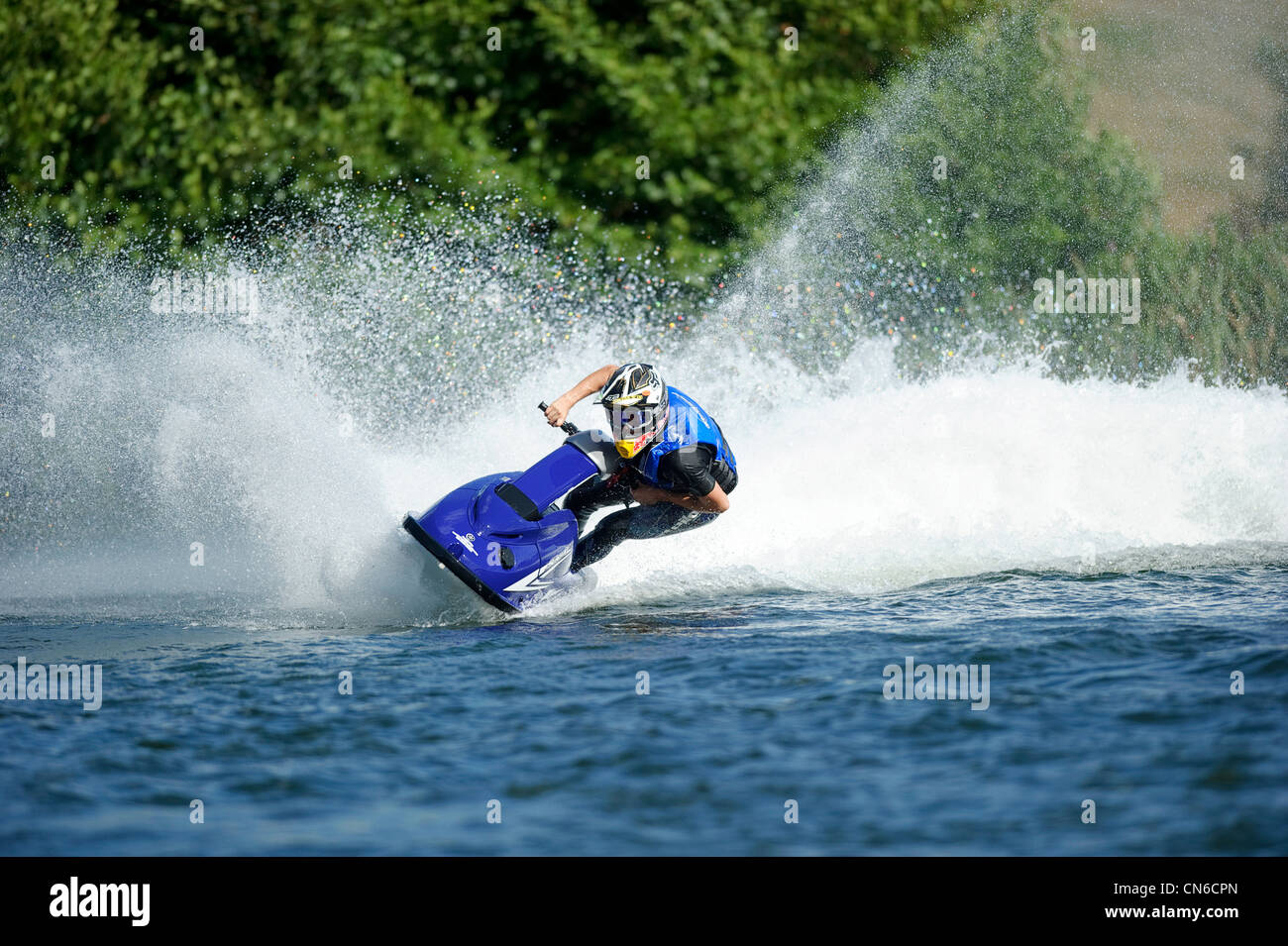 2b0dc830e3154 jet skiing across lake with water spray behind - Stock Image