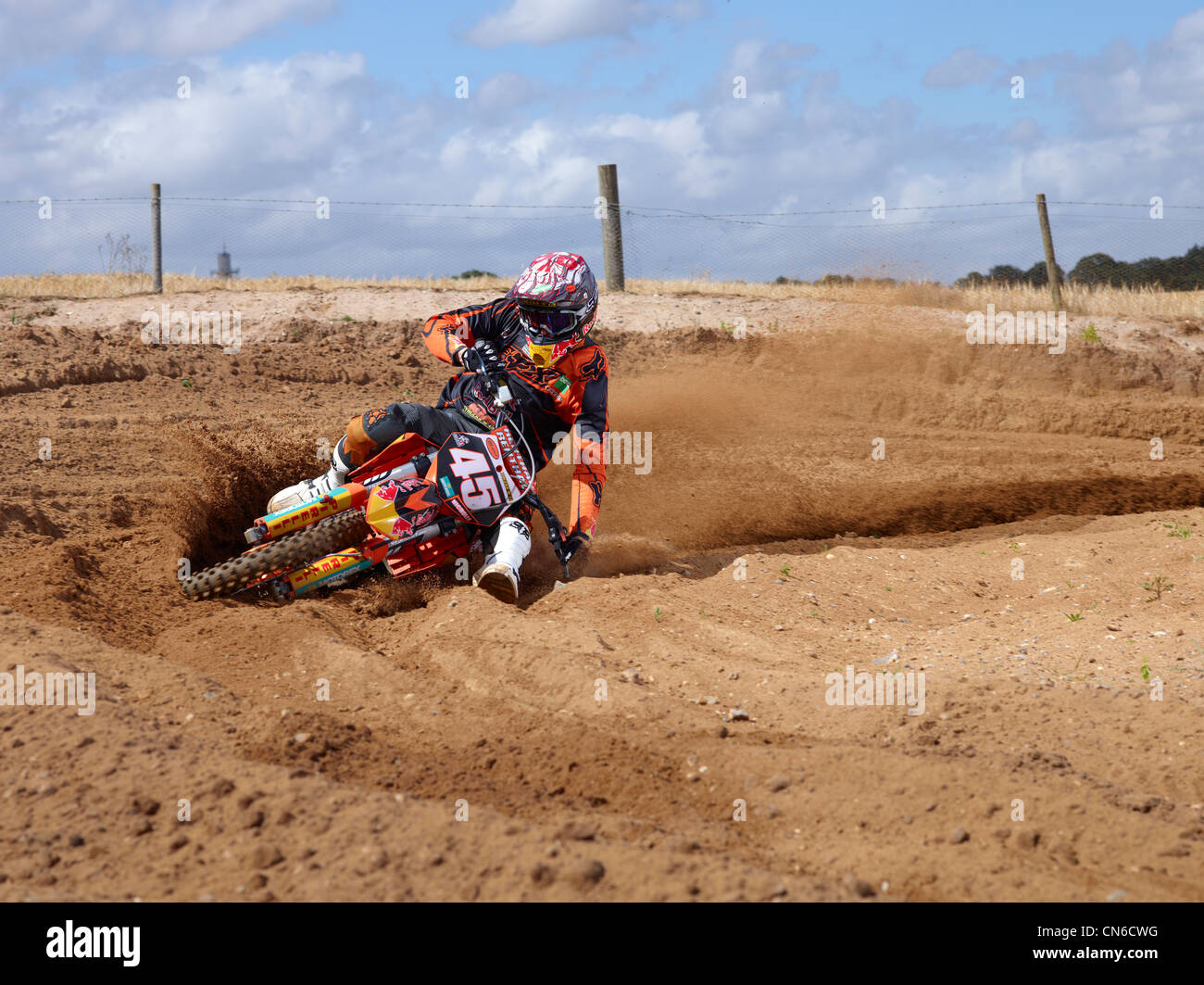 motorcross bike racing around dirt corner, speeding winning - Stock Image