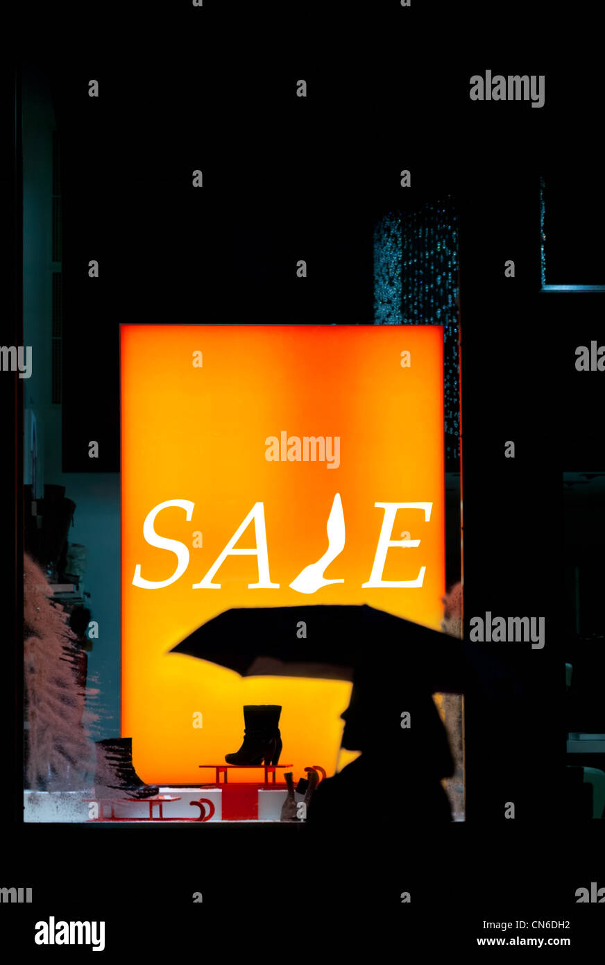 Silhouette of a passerby on storefront with sale inscription - Stock Image