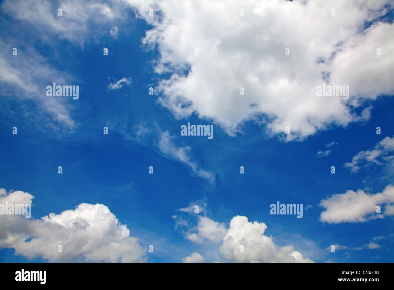 White fluffy clouds in the deep blue sky. - Stock Image