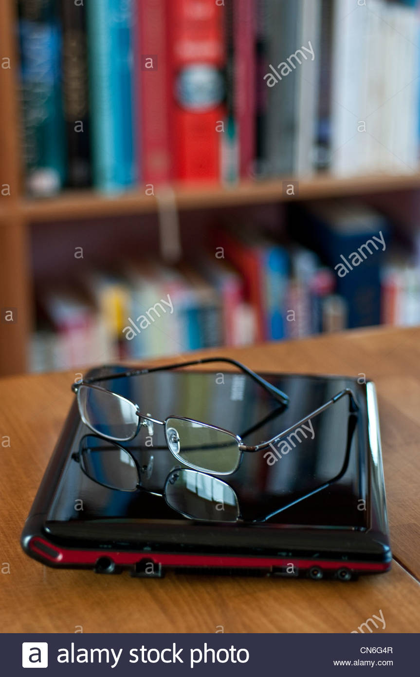 Glasses on a laptop and a bookshelf behind - Stock Image