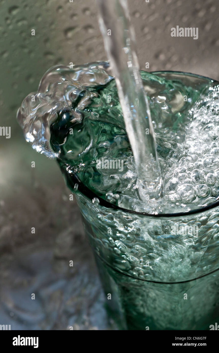 Tumbler glasses overflowing with bubbling water - Stock Image