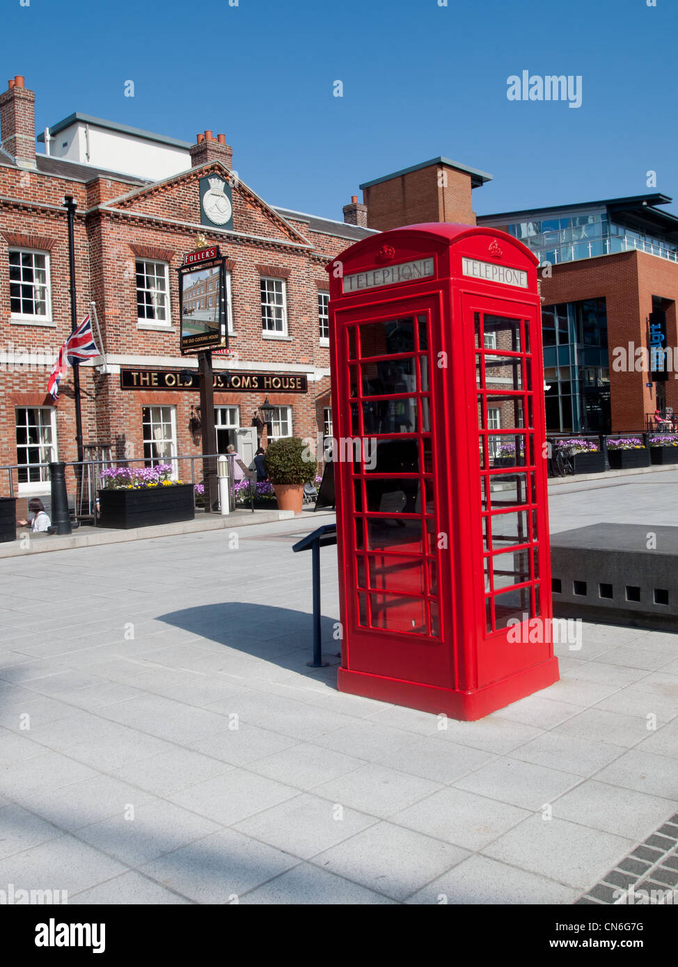 A red telephone box in front a public house in England - Stock Image