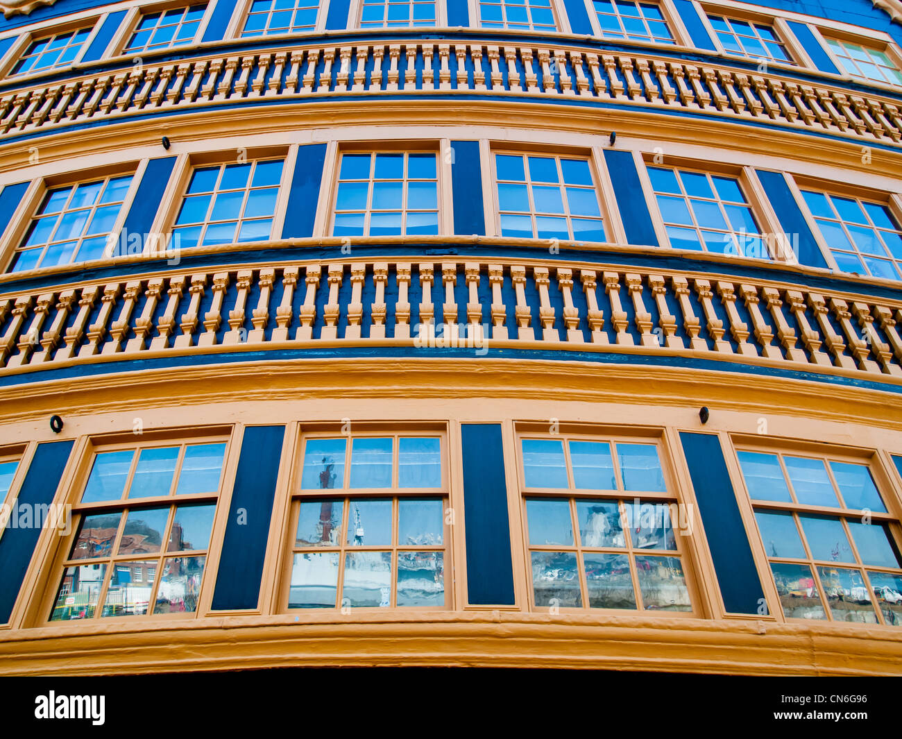 The stern windows of HMS Victory in Portsmouth historic dockyard reflecting modern warships Stock Photo