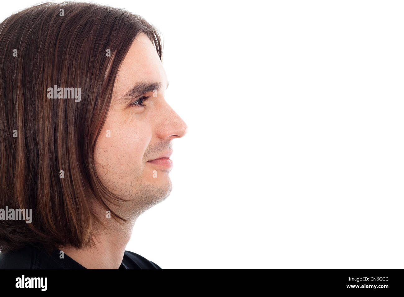 Profile of young long haired man neutral smiling relaxed face, isolated on white background with large copy space. - Stock Image