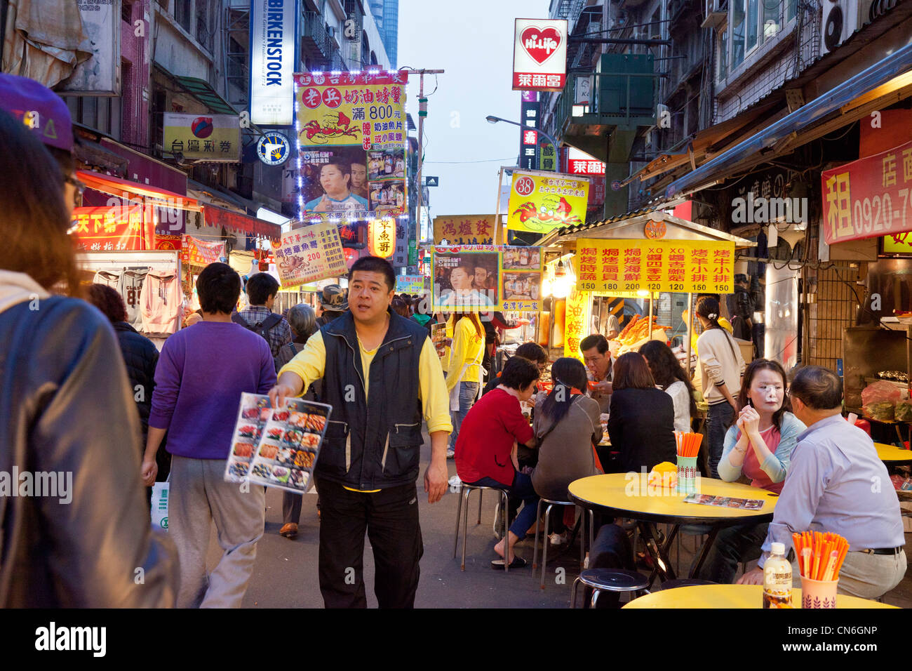 Man touting for restaurant business in Keelung (Jilong) Temple Plaza Night Market, Miaokou Yeshi, Keelung Taiwan. - Stock Image