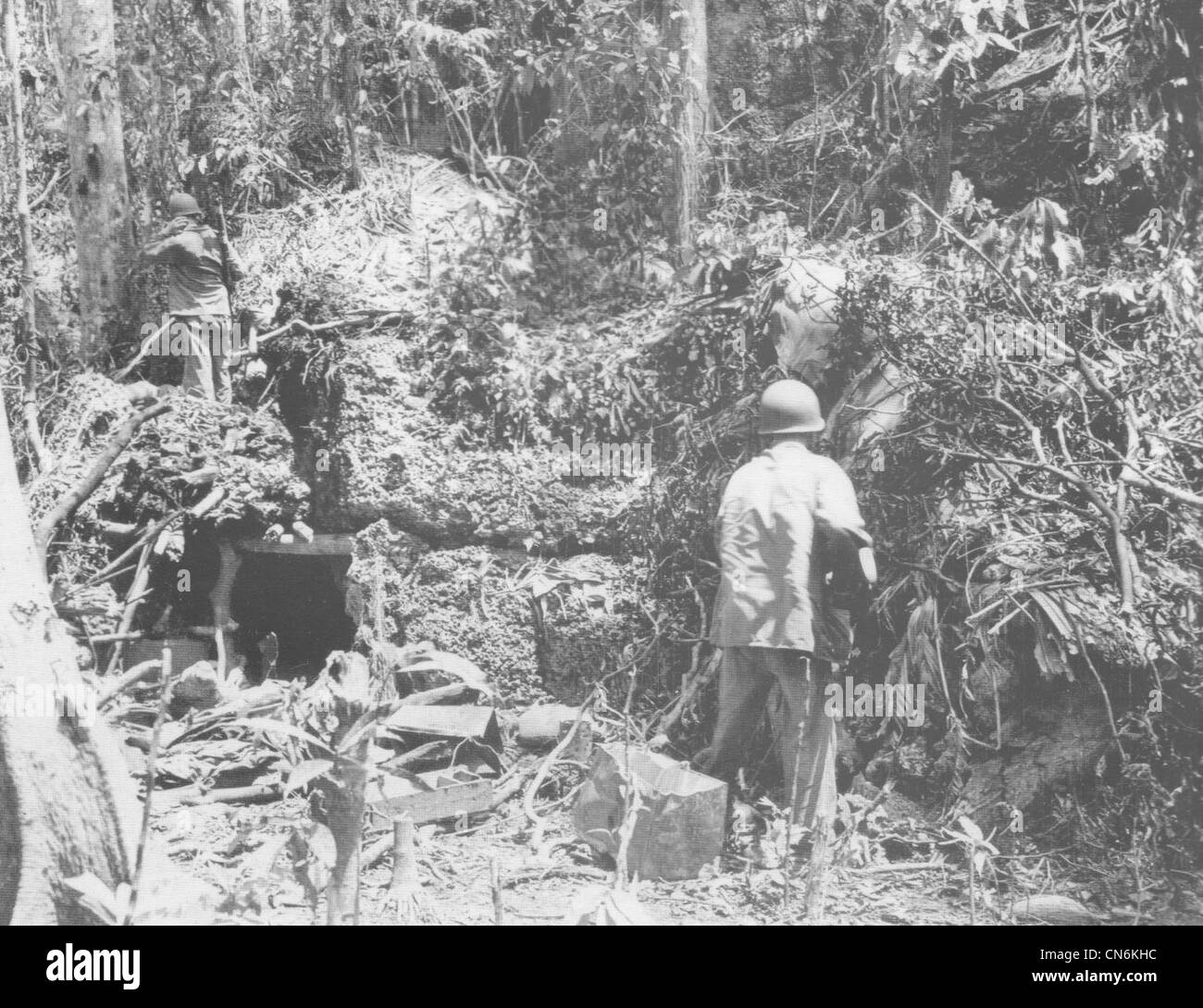 Two U S  Marines check a Japanese bunker constructed of coral blocks