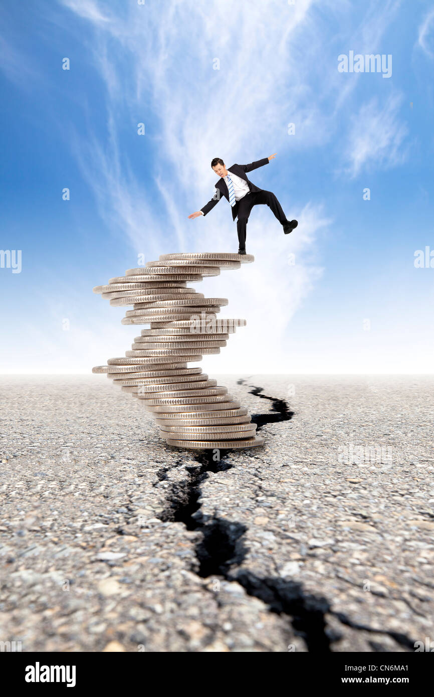 busines and Economic crisis concept. cracked road and unstable businessman on the money tower - Stock Image