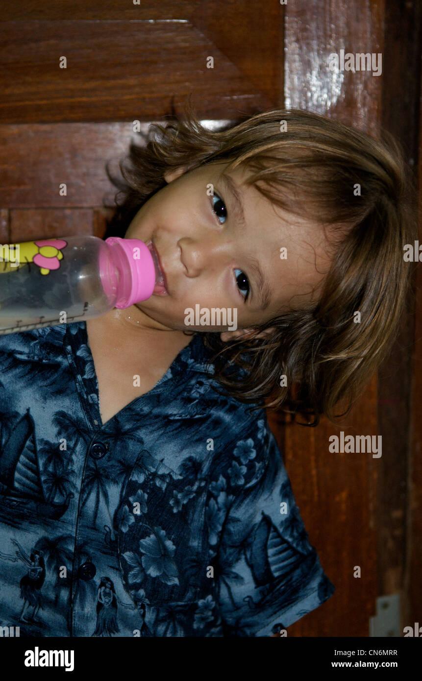 2 1/2 year old mixed race boy drinking from milk bottle, Phnom Penh,  Cambodia. credit: Kraig Lieb