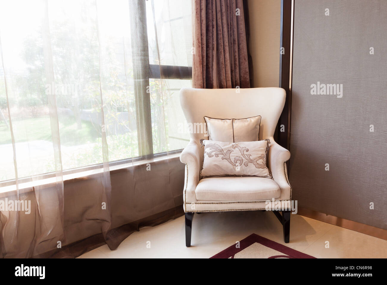 Armchair close to the window at a new interiors, through the window a small garden can be seen. - Stock Image