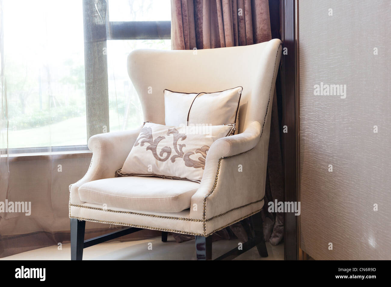 Armchair close to the window at a new interiors - Stock Image