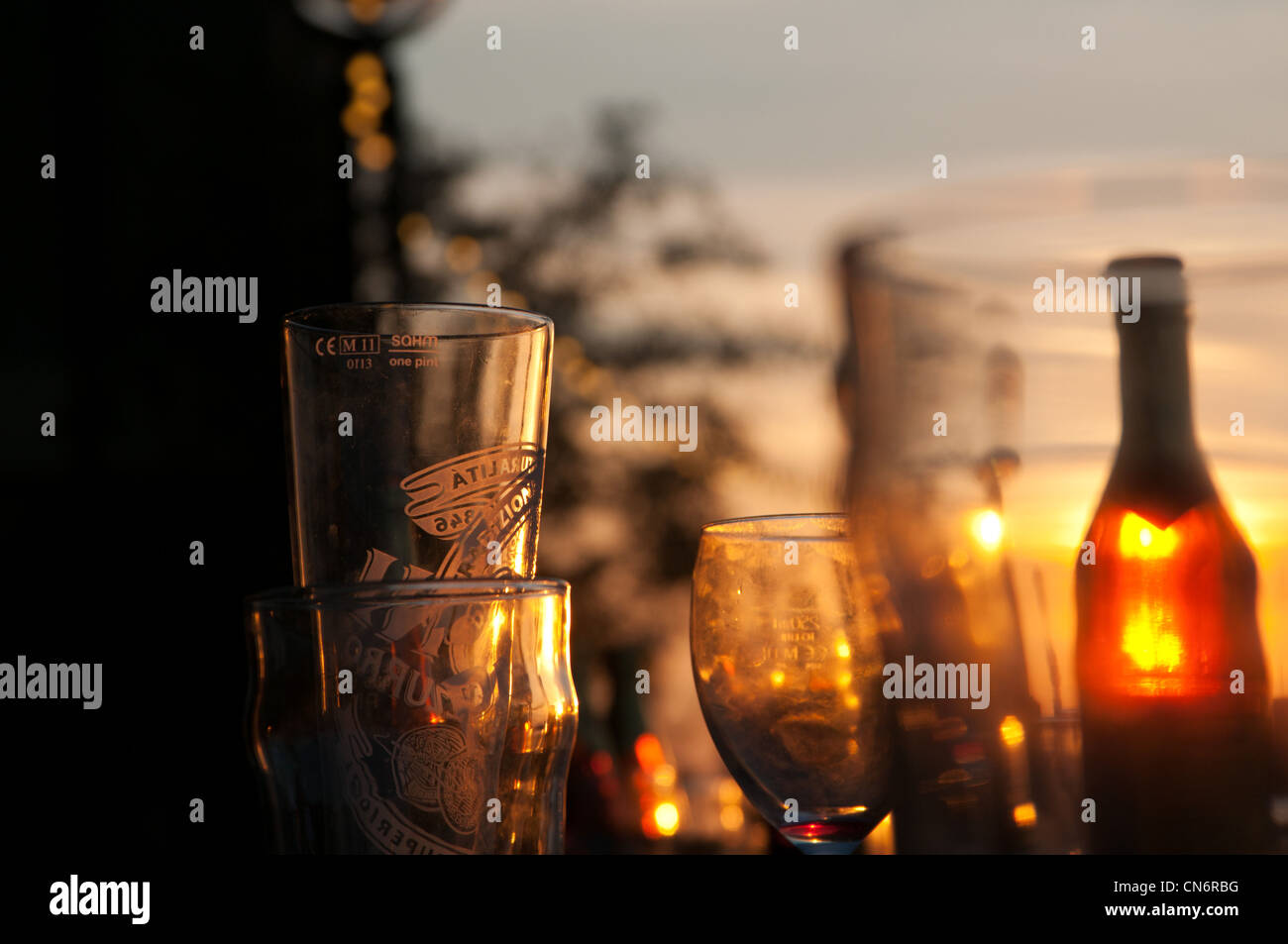 Empty pint glasses in the warm light of a London sunset. - Stock Image