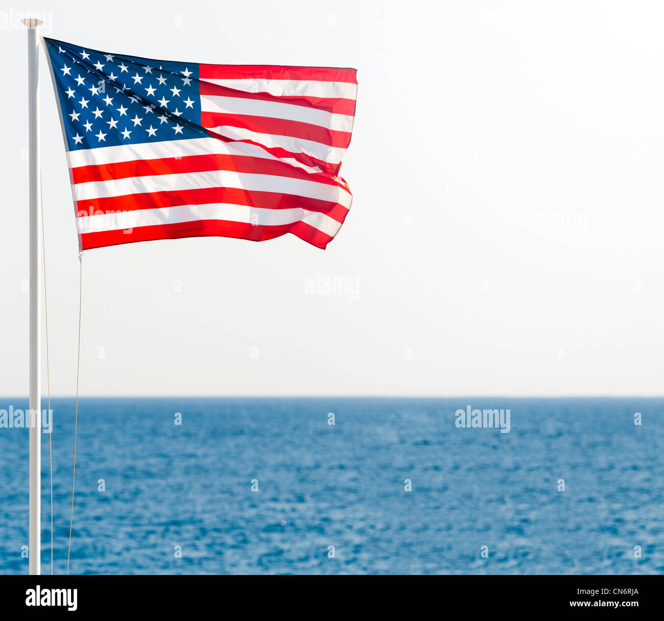 b9213e95bb17 united states of america flag on pole with blue sea in background and clear  sky. Lots of copy space.