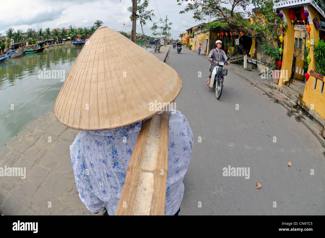 Woman carrying yoke baskets of fruit in street, Hoi An, Vietnam - Stock Image