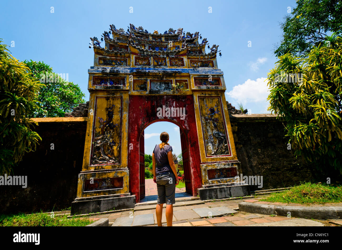 Young women looking into one of many gates surrounding the Forbidden Purple City, UNESCO World Heritage Site, Hue, - Stock Image