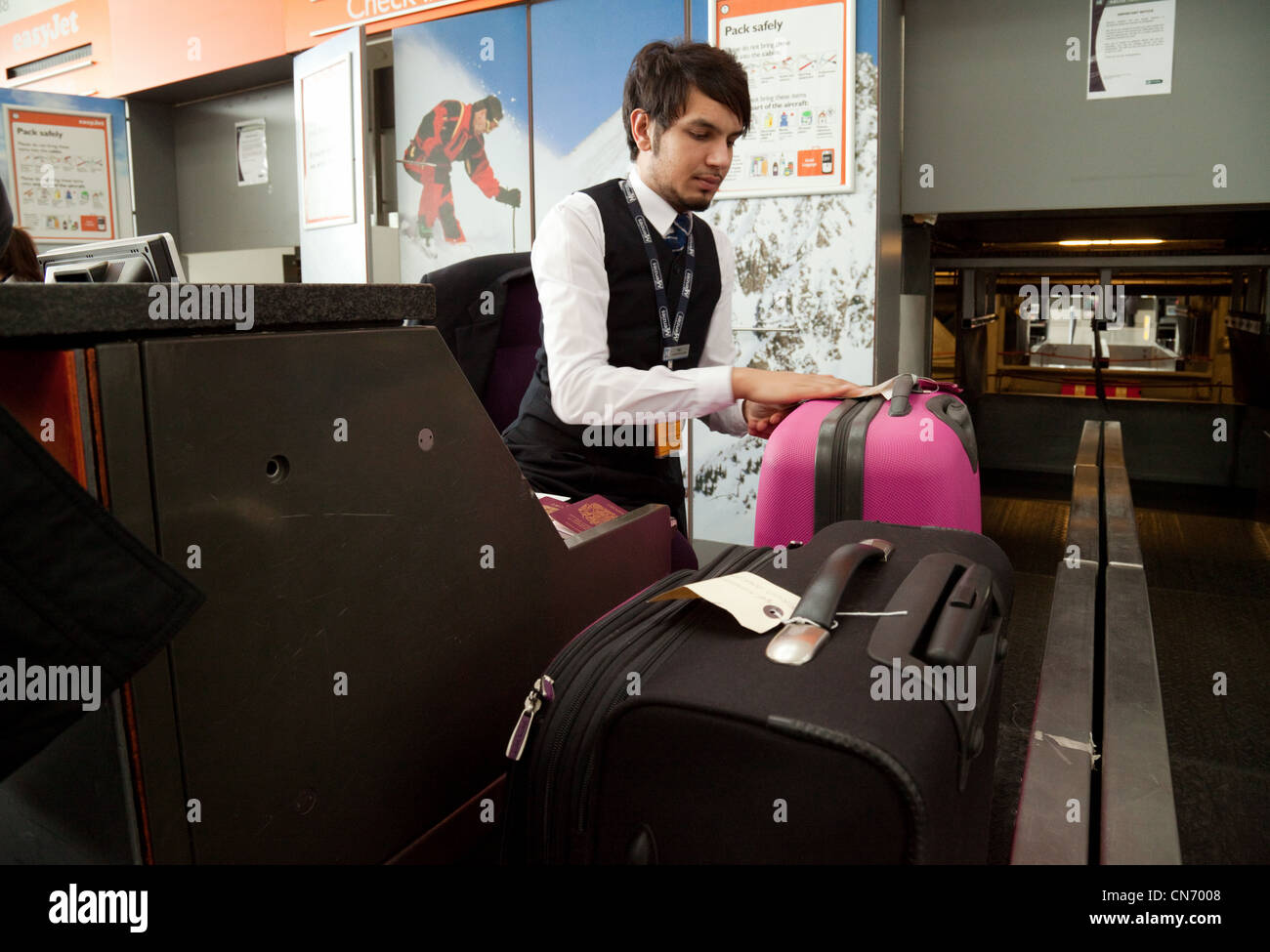 Baggage check in Easyjet staff at Stansted Airport Essex UK - Stock Image