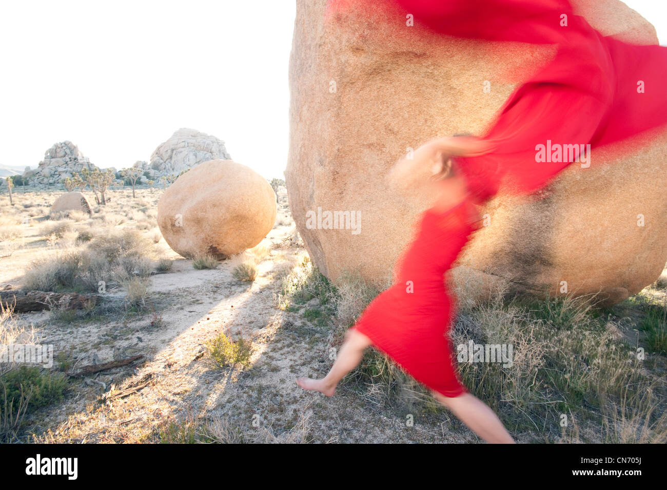Blurred red woman throwing her red scarf into a stone landscape. - Stock Image