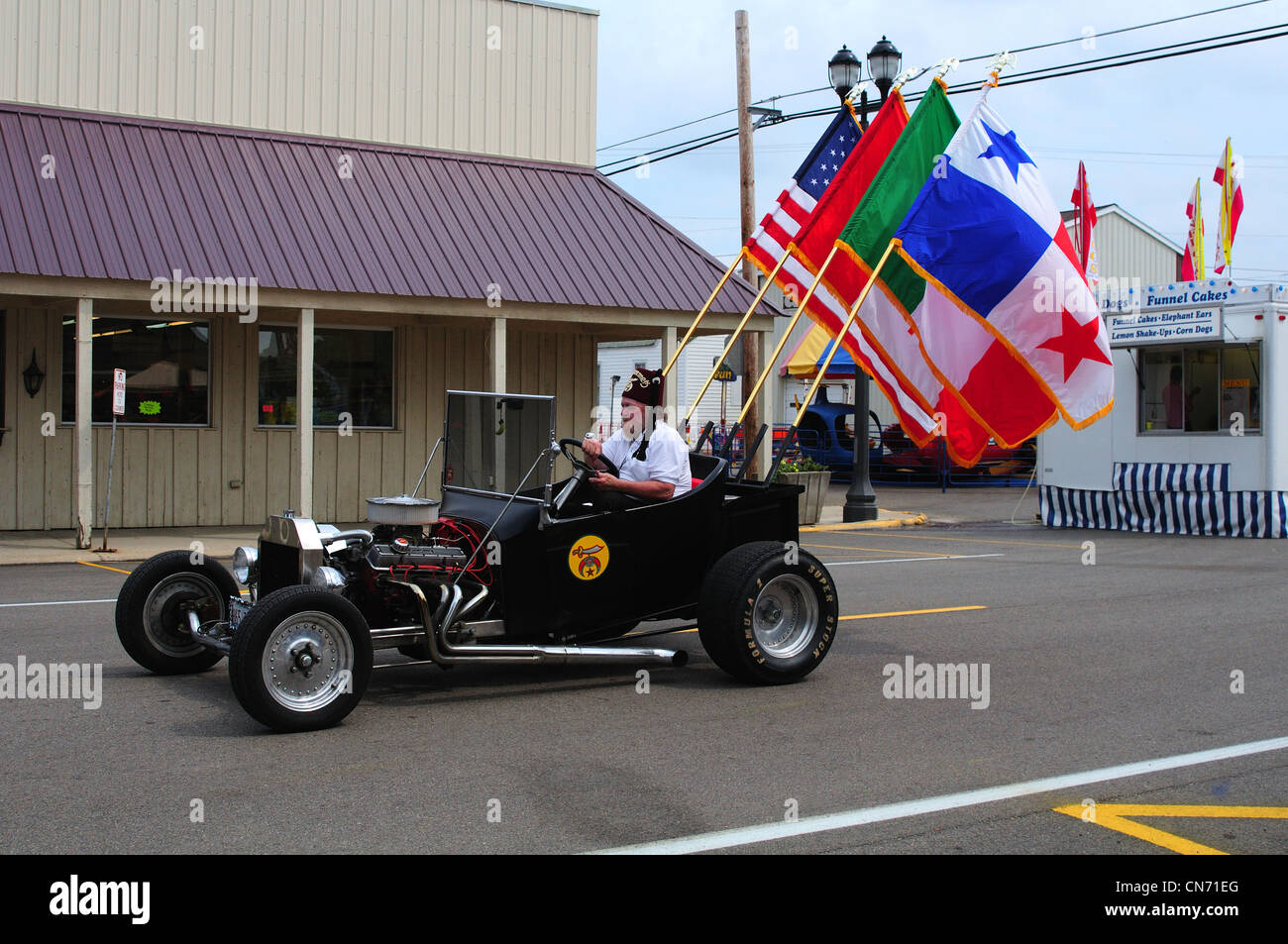 A Shriner driving a t-bucket roadster in a summer parade - Stock Image