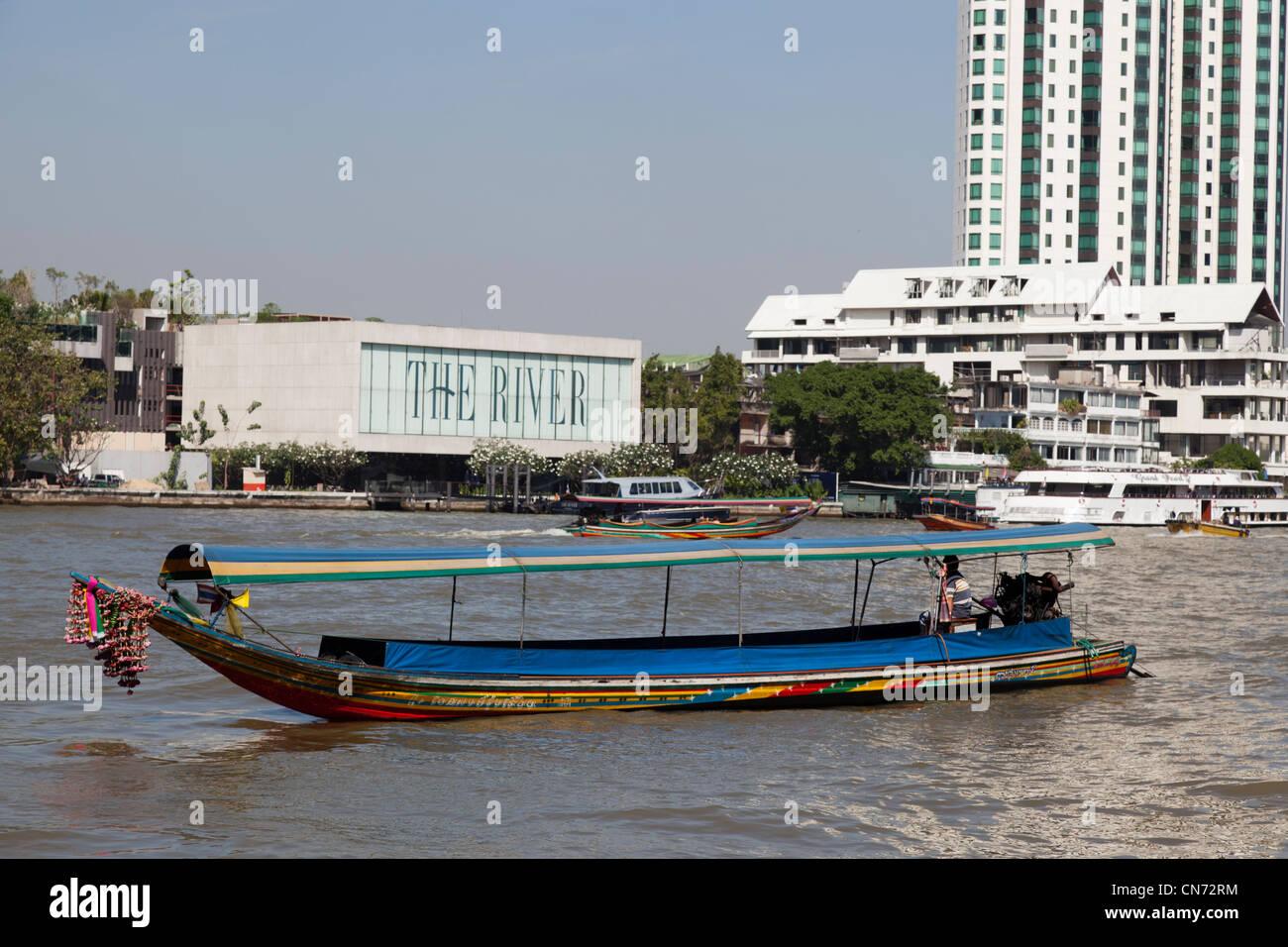 "A long-tail boat in search of tourists on the Chao Phraya river (Bangkok). Bateau dit ""à longue queue"" sur le fleuve Stock Photo"