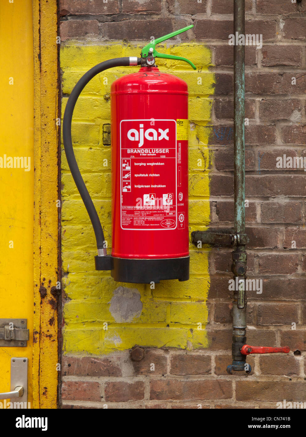 Fire extinguisher hanging in the designated place in old factory in Groningen, the Netherlands - Stock Image