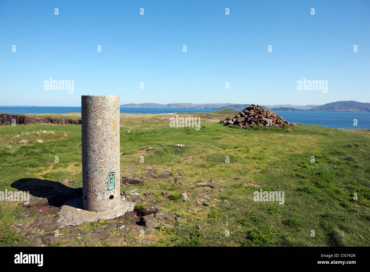 Trig point and cairn at the highest point on Staffa in the Inner Hebrides of Scotland with views to the Isle of - Stock Image