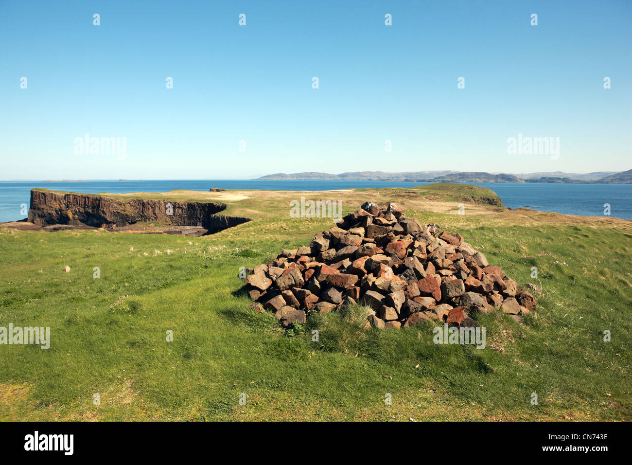 Cairn at the flat grassy top of the Isle of Staffa in the Inner Hebrides of Scotland with views to the Isle of Mull - Stock Image