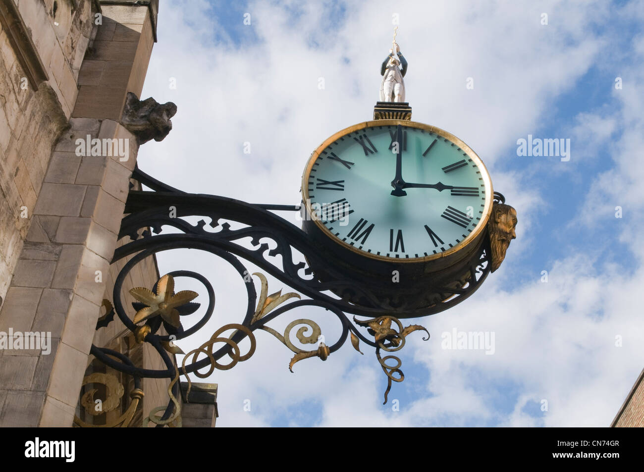 Low angle view of historic Little Admiral Clock (hands at 3.00pm) bracketed high on stone exterior wall of church - Stock Image