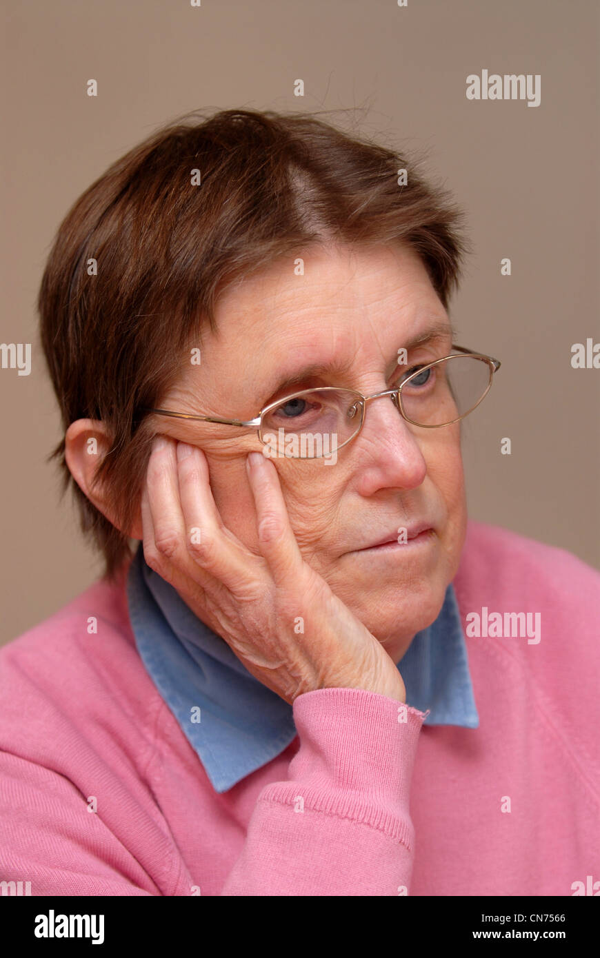 Elderly woman sitting down resting her hand on her face, Reading, UK. - Stock Image
