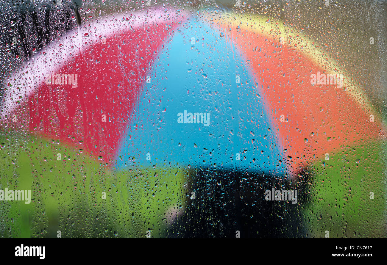 Raindrops on a window pane with a person holding a rainbow coloured umbrella outside - Stock Image